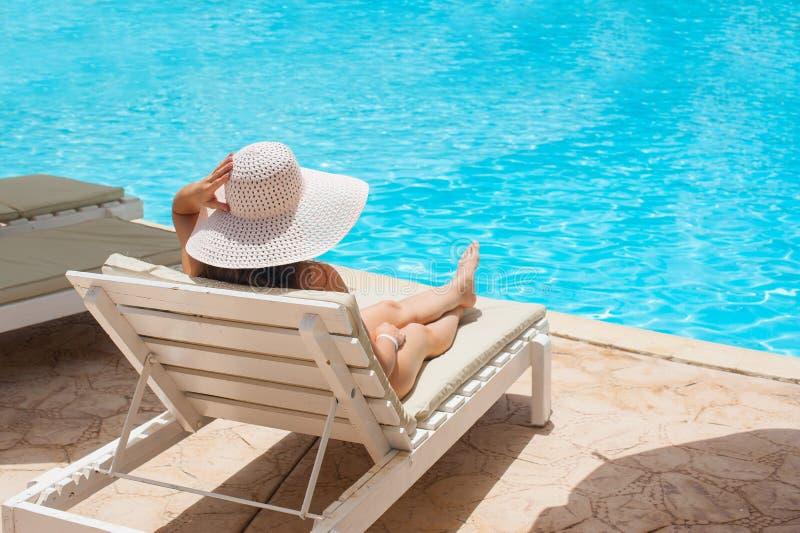 Kvinna i den vita hatten som ligger på en dagdrivare nära simbassängen royaltyfri fotografi