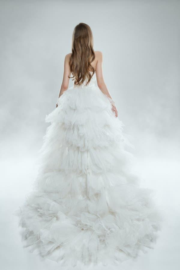 Kvinna i den vita klänningbaksidasikten, modemodell i den långa kappan, skott för bröllop för brudskönhetstudio royaltyfri fotografi
