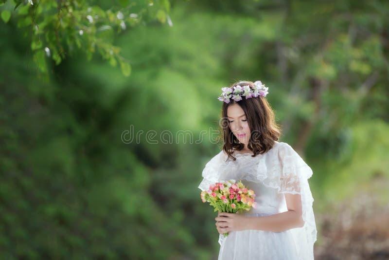 Kvinna i den vita klänningen med blomman arkivfoto