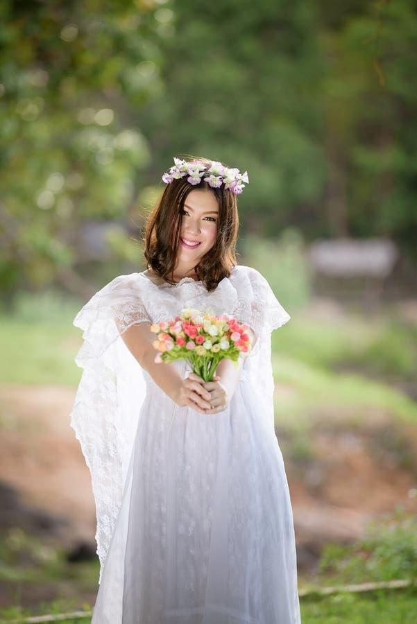 Kvinna i den vita klänningen med blomman royaltyfri fotografi