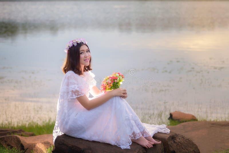 Kvinna i den vita klänningen med blomman royaltyfri foto