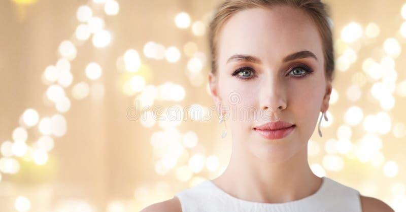 Kvinna i den vita klänningen med diamantörhänget royaltyfri foto
