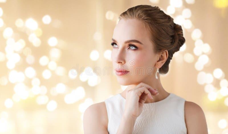Kvinna i den vita klänningen med diamantörhänget arkivfoto