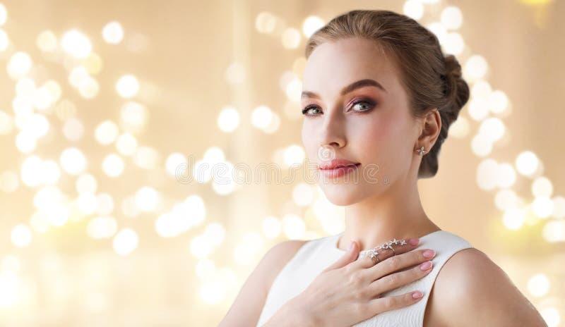Kvinna i den vita klänningen med diamantsmycken arkivfoto