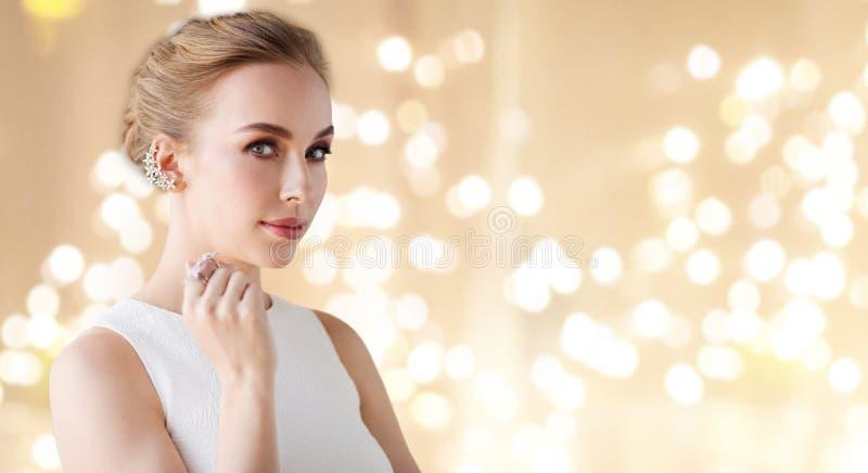Kvinna i den vita klänningen med diamantsmycken royaltyfri foto