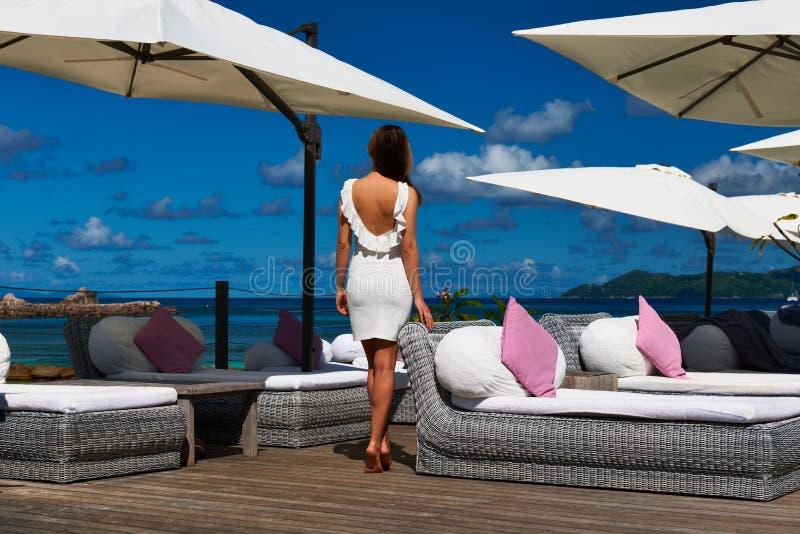 Kvinna i den vita klänningen nära poolside arkivfoto