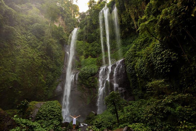 Kvinna i den vita klänningen på de Sekumpul vattenfallen i djungler på lodisar royaltyfri fotografi