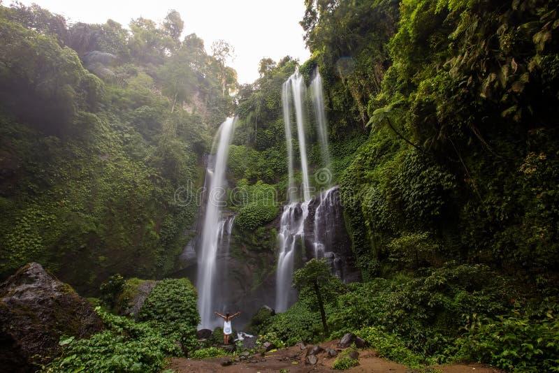 Kvinna i den vita klänningen på de Sekumpul vattenfallen i djungler på lodisar royaltyfri bild