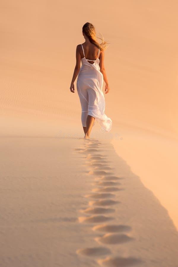 Kvinna i den vita klänningen som går på öken fotografering för bildbyråer