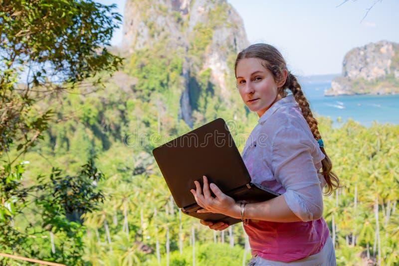 Kvinna i den vita skjortan med den svarta bärbara datorn på överkanten av kullen Avlägset frilans- arbete, touristic skapa för ru arkivfoto
