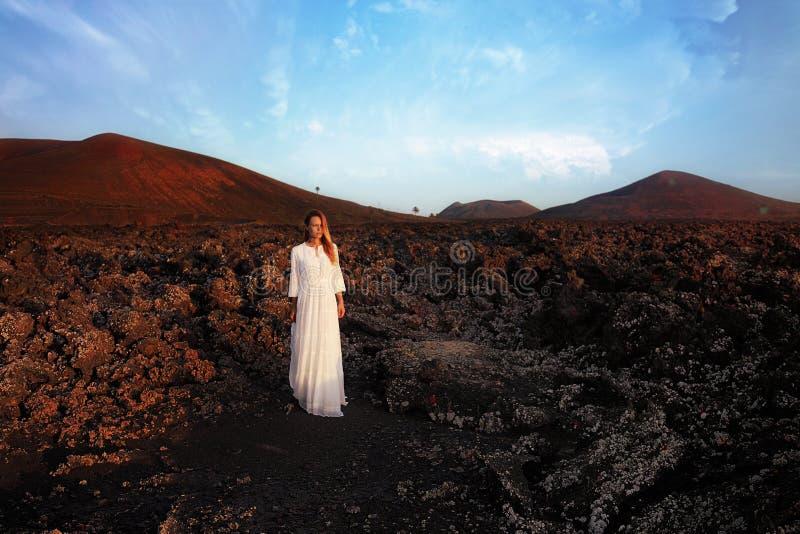 Kvinna i det vita klänninganseendet på kullen breathink med stängda ögon Lanzarote kanariefågelöar, Spanien fotografering för bildbyråer