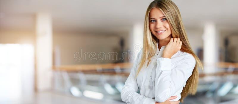 Kvinna i det vita skjortaanseendet i korridoren av affärsmitten royaltyfri bild