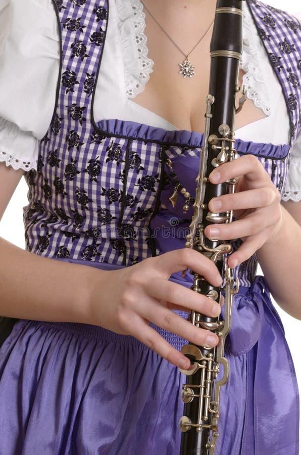 Kvinna i dirndlklänningen som spelar klarinetten, detalj royaltyfri bild