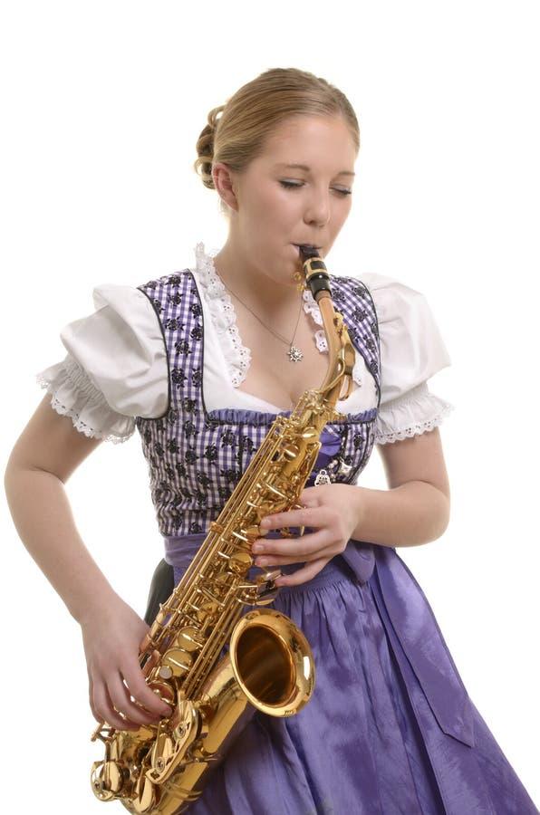Kvinna i dirndlklänningen som spelar saxofonen royaltyfri foto