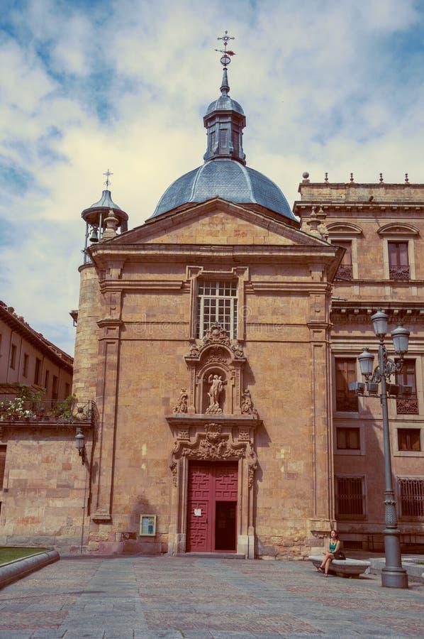 Kvinna i en bänk som är främst av gammal byggnad på Salamanca arkivbild