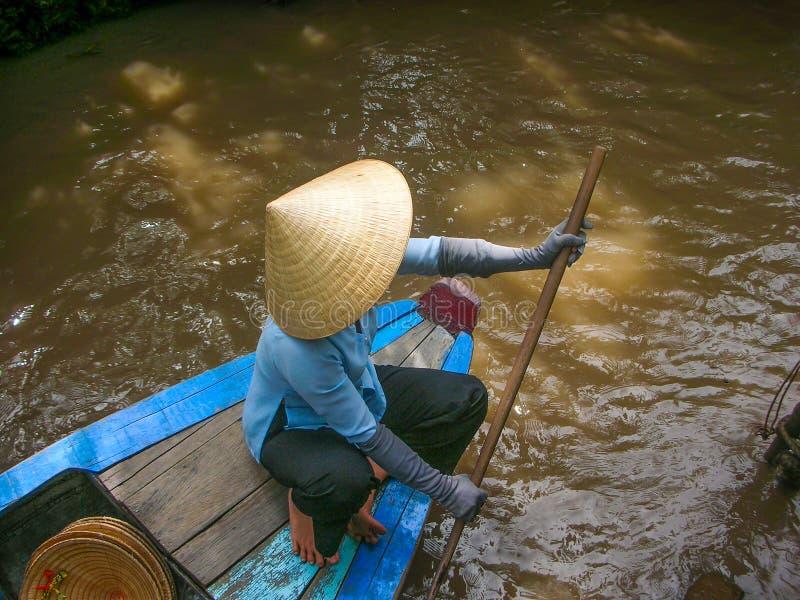 Kvinna i en barkass i Vietnam med hennes tipycal hatt arkivbild