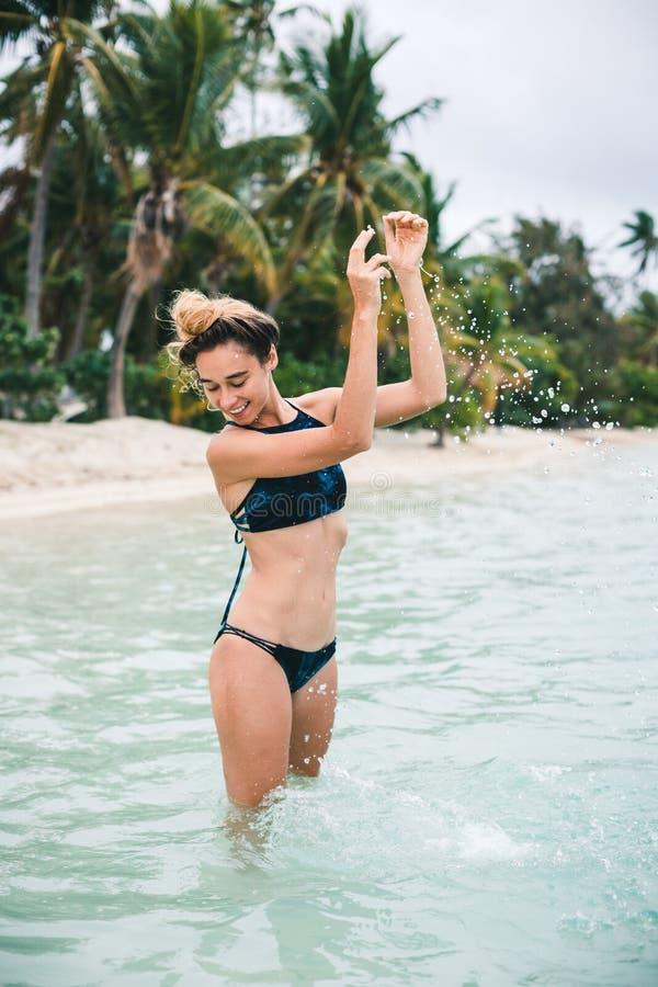 Kvinna i en bikini på beacch med en bakgrund av palmträd royaltyfria bilder