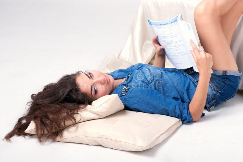 Kvinna i en blå grov bomullstvillskjorta som läser en bok som ligger på golvet fotografering för bildbyråer