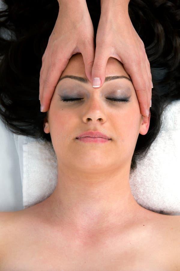 Kvinna i en brunnsort som får en head massage. arkivfoton