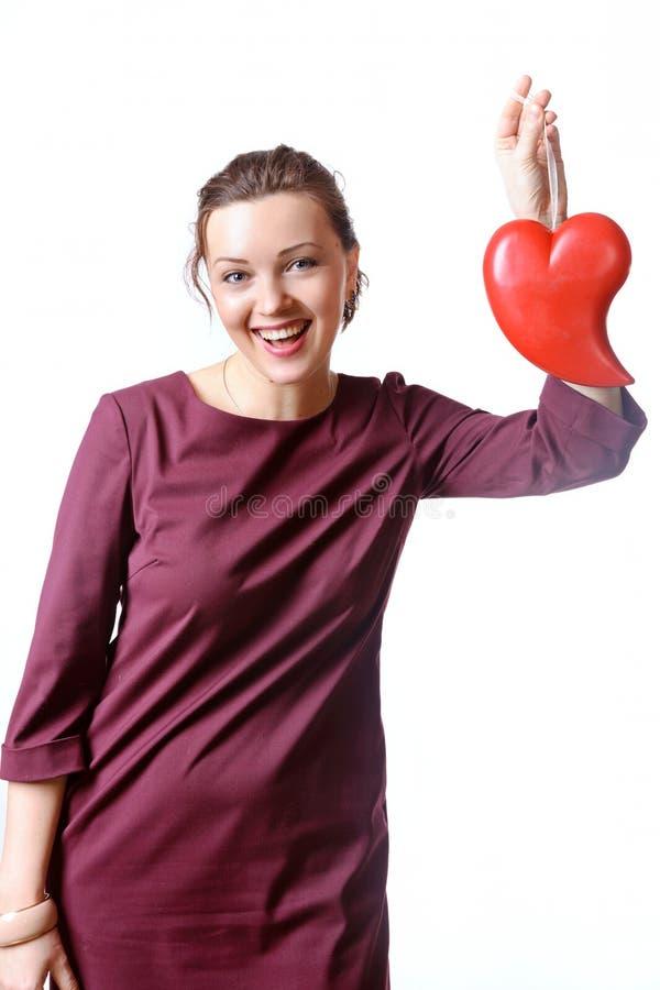 Kvinna i en burgundy klänning som skrattar hållande hjärta i hennes hand arkivfoto