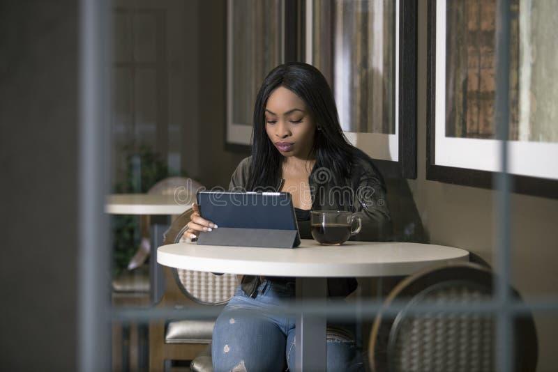 Kvinna i en coffee shop med en minnestavla royaltyfri fotografi