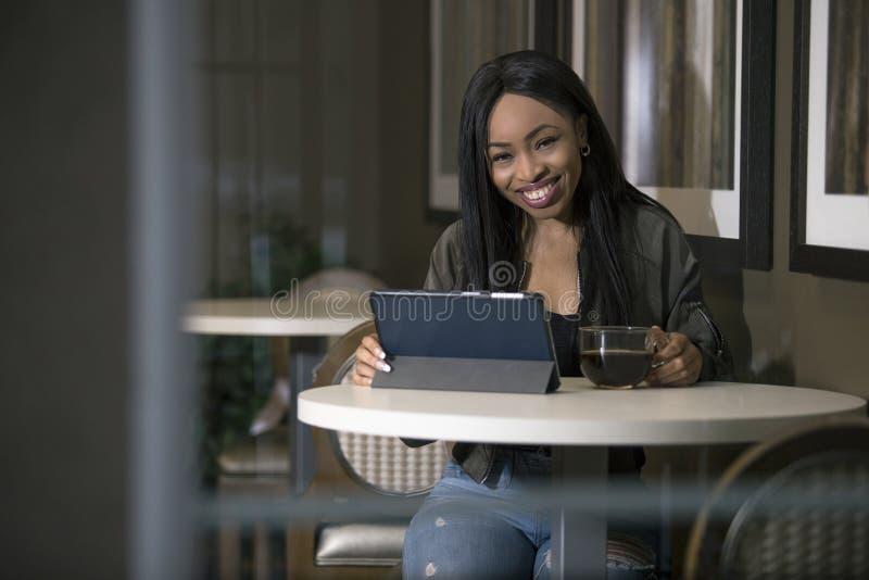 Kvinna i en coffee shop med en minnestavla arkivbild