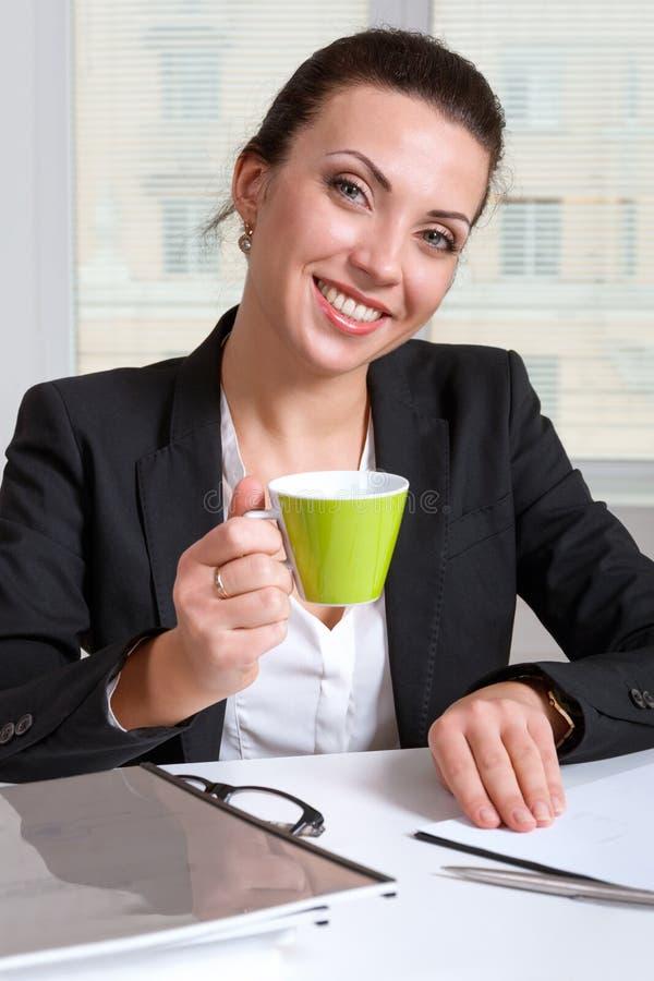 Kvinna i en dräkt som dricker en kopp kaffe och le royaltyfria bilder