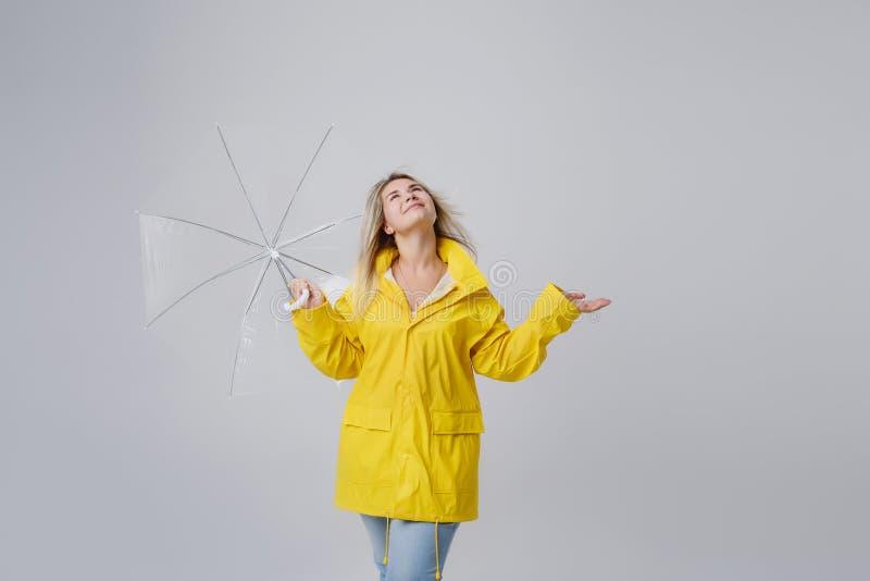 Kvinna i en gul regnrock på en grå bakgrund arkivbild