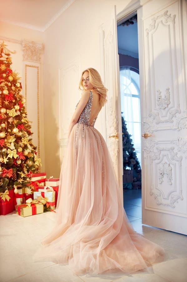 Kvinna i en länge kräm-färgad klänning och att stå nära julgranen och dörren Den lyxiga blondinen i aftonklänning firar arkivfoto