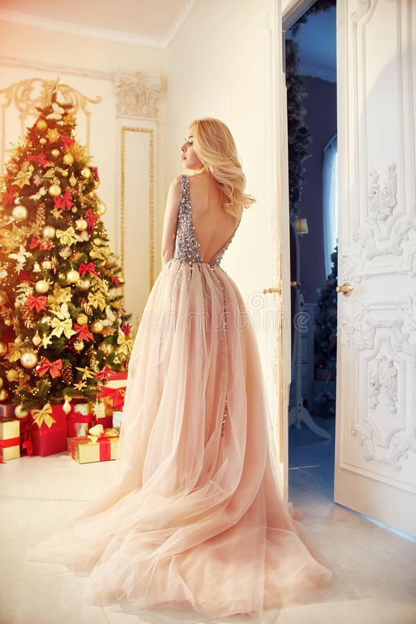 Kvinna i en länge kräm-färgad klänning och att stå nära julgranen och dörren Den lyxiga blondinen i aftonklänning firar royaltyfria foton