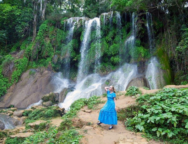 Kvinna i en lång klänning nära vattenfall Soroa, Pinar del Rio, Kuba royaltyfri bild