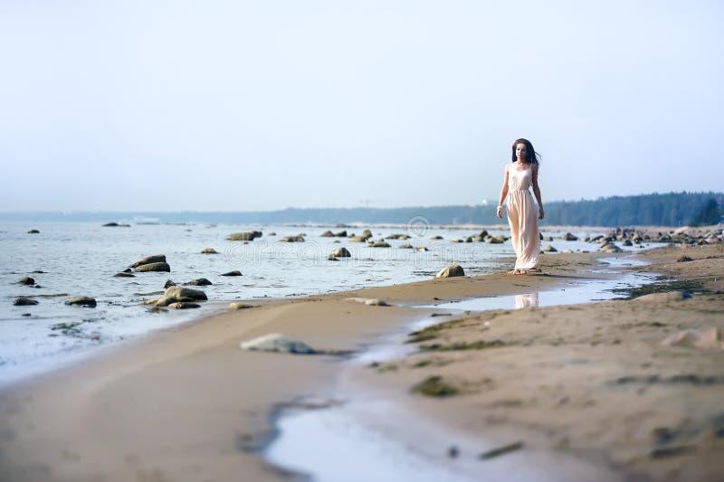Kvinna i en lång klänning på kusten royaltyfria bilder