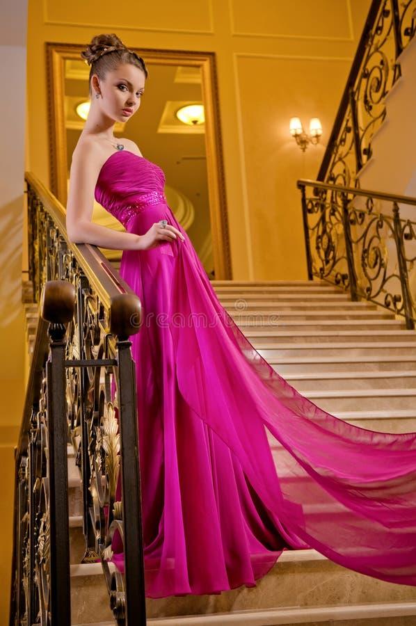 Kvinna i en lång klänning som ligger på trappan arkivfoton