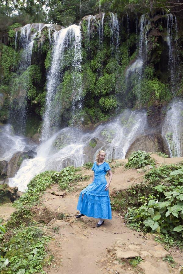 Kvinna i en l?ng kl?nning n?ra vattenfall Soroa, Pinar del Rio, Kuba arkivfoto