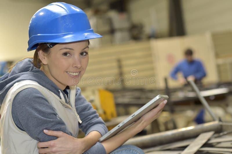 Kvinna i en metallurgisk fabrik genom att använda minnestavlan royaltyfri bild