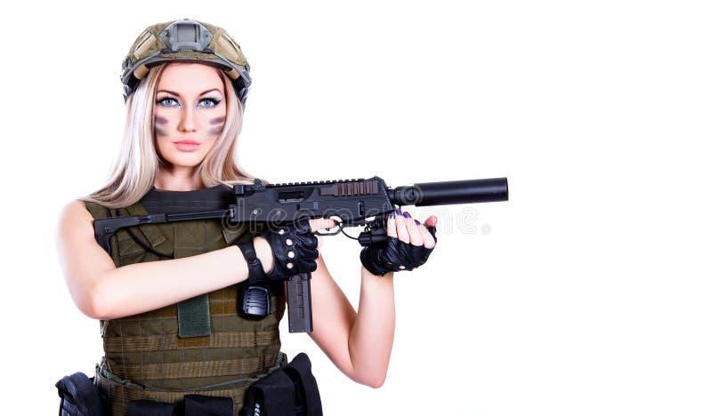 Kvinna i en militär kamouflage som rymmer smgen arkivbild