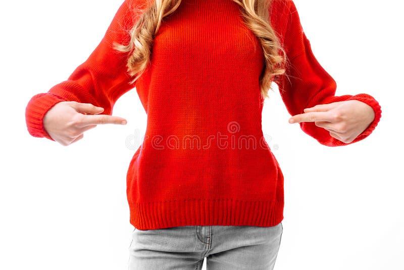Kvinna i en röd jultröja som pekar till en tröja med fingrar På en vit bakgrund royaltyfri foto