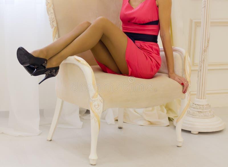 Kvinna i en röd klänning på en vit stol fotografering för bildbyråer
