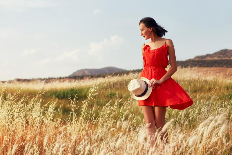 Kvinna i en röd klänning som går på fältet på en varm sommarafton Gult gräs på solnedgången, flickan som rymmer en hatt i hans hä royaltyfri fotografi