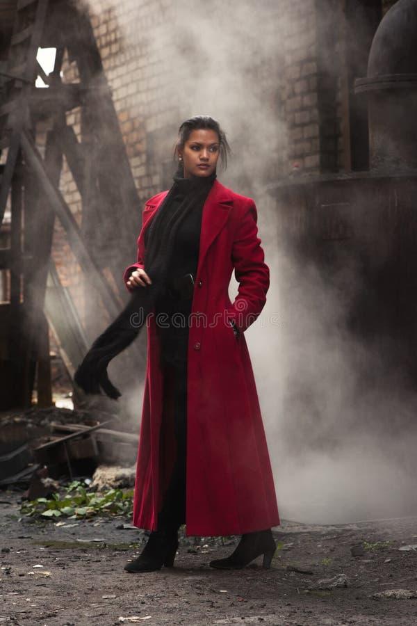 Kvinna i en röd regnrock royaltyfria foton