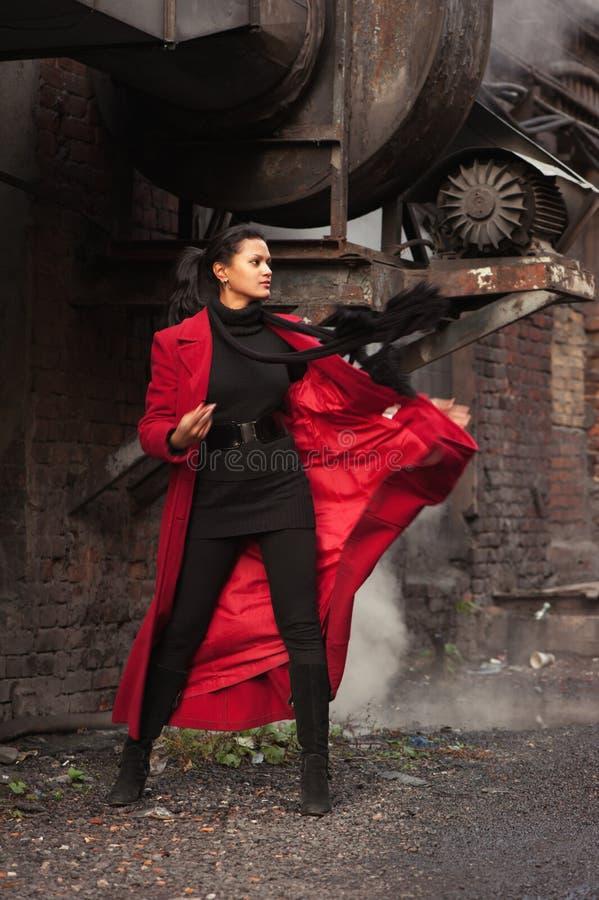 Kvinna i en röd regnrock royaltyfri foto
