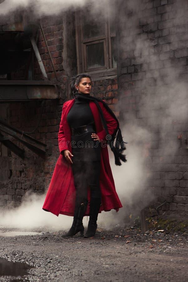 Kvinna i en röd regnrock arkivbilder