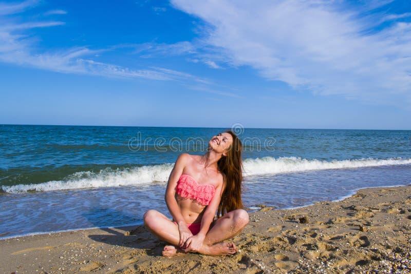 Kvinna i en rosa baddräkt på stranden, nära havet royaltyfria bilder