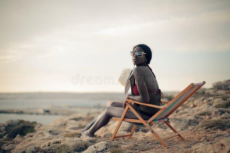 Kvinna i en solstol arkivfoton
