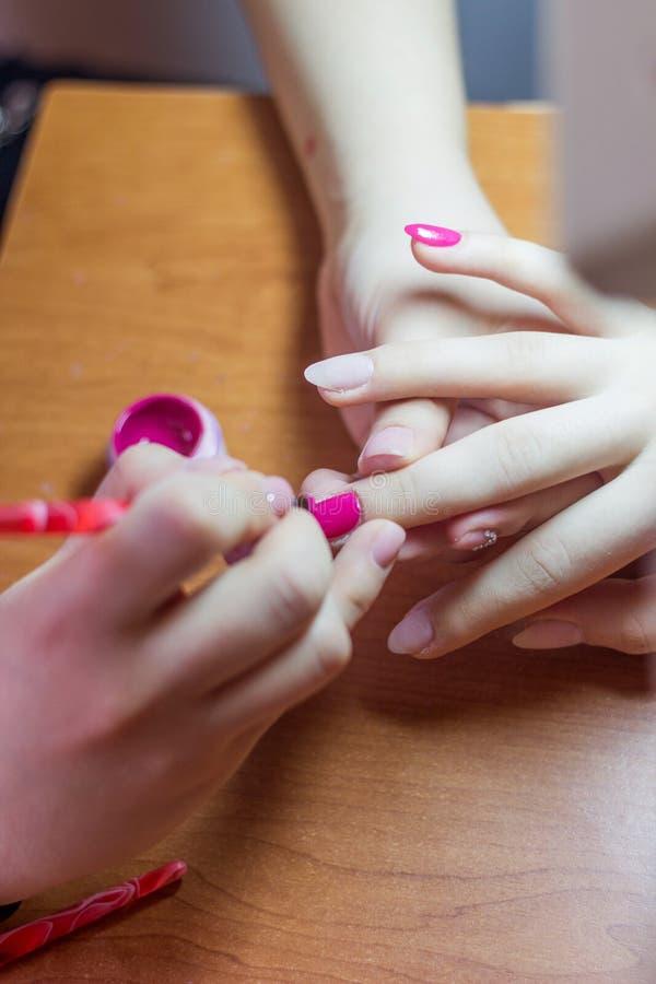 Kvinna i en spikasalong som mottar en manikyr av en kosmetolog arkivfoton