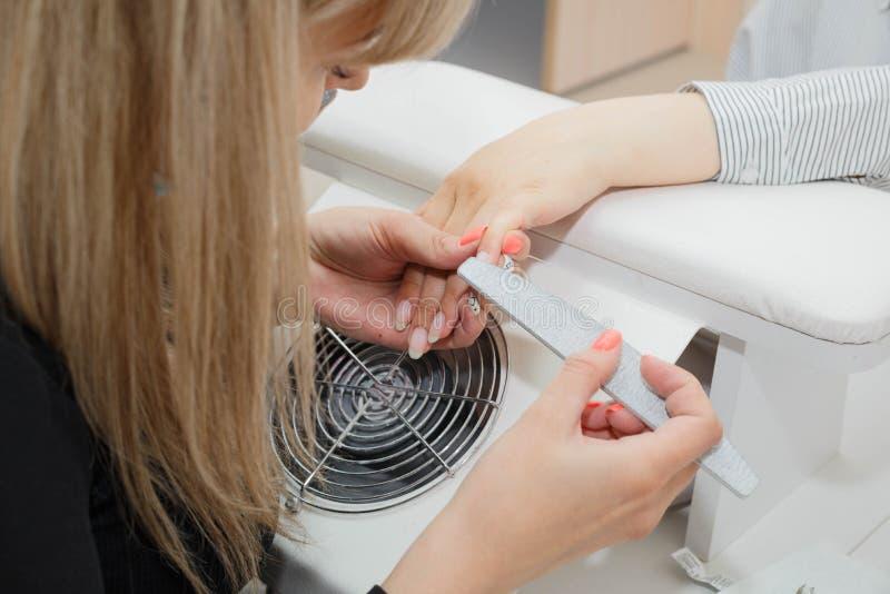 Kvinna i en spikasalong som mottar en manikyr av en kosmetolog arkivbild