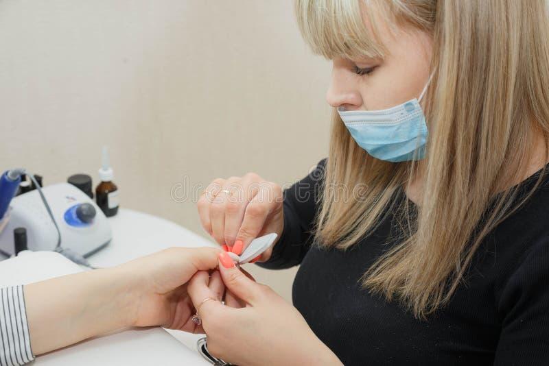 Kvinna i en spikasalong som mottar en manikyr av en kosmetolog arkivbilder
