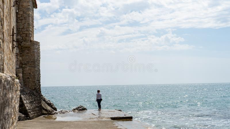 Kvinna i en stenport i en gammal stad av Adriatiskt havet Vatten i vaggar pir och den medeltida väggen utanför befästningen flick royaltyfri foto