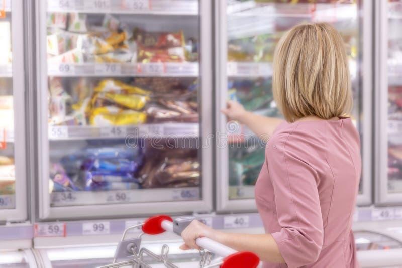 Kvinna i en supermarket i avdelningen för djupfryst mat N?rbild arkivbild