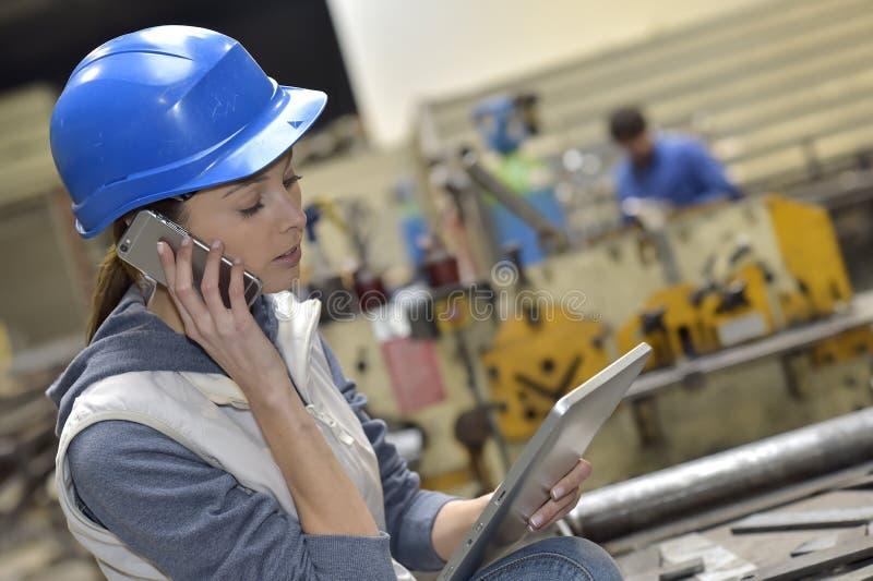 Kvinna i en tillverkning som talar på telefonen arkivbilder